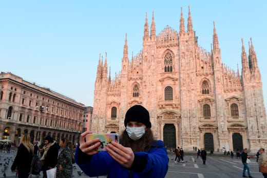 A woman wearing a protective facemask takes a selfie picture in the Piazza del Duomo in central Milan, on Feb. 24, 2020, following security measures taken in northern Italy against the COVID-19 the novel coronavirus.