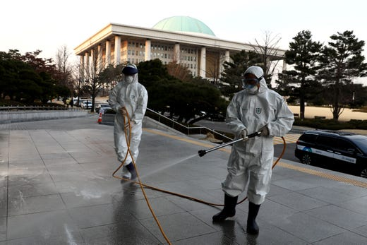 Disinfection professionals wear protective suits whilst spraying an anti-septic solution against the coronavirus (COVID-19) at a National Assembly on Feb. 24, 2020 in Seoul, South Korea.
