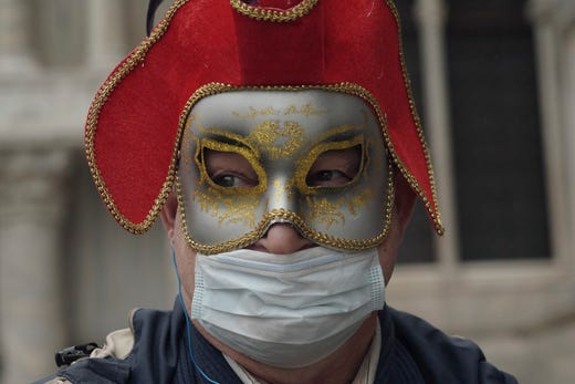 A Russian tourist dons both a carnival mask and a protective face mask as he visits St. Mark's square Venice, Italy, Feb. 25, 2020. Italy has been scrambling to check the spread of Europe's first major outbreak of the new viral disease amid rapidly rising numbers of infections and calling off the popular Venice Carnival and closing tourist attractions.
