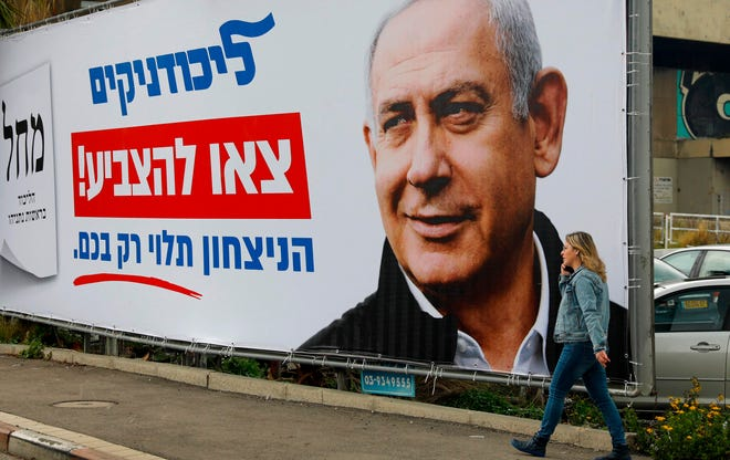 An Israeli woman walks past an electoral poster of Israel's Prime Minister Benjamin Netanyahu, in the northern Israeli city of Haifa on Feb. 23, 2020.