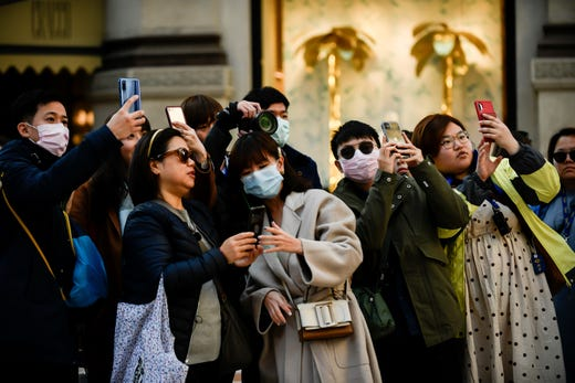 People, some wearing sanitary masks, take photos in central Milan, Italy, Feb. 24, 2020.