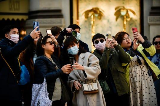 Menschen, von denen einige Hygienemasken tragen, fotografieren am 24. Februar 2020 in Zentral-Mailand, Italien.