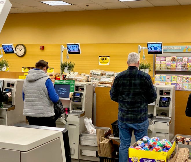Shoppers at the Harvard Market, down the street from Amazon's Go Grocery store in Seattle, pay for their food on the self-checkout machines