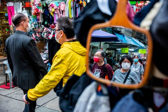 People wearing protective face masks walk through a market in the wan chai district of Hong Kong on February 25, 2020. The new coronavirus has peaked in China but could still grow into a pandemic, the World Health Organization warned, as infections mushroom in other countries.