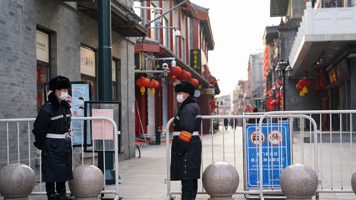 Chinese security guards wear protective masks on an empty commercial street in Beijing on Feb, 25, 2020 .