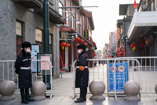 Chinese security guards wear protective masks on an empty commercial street in Beijing on Feb. 25.