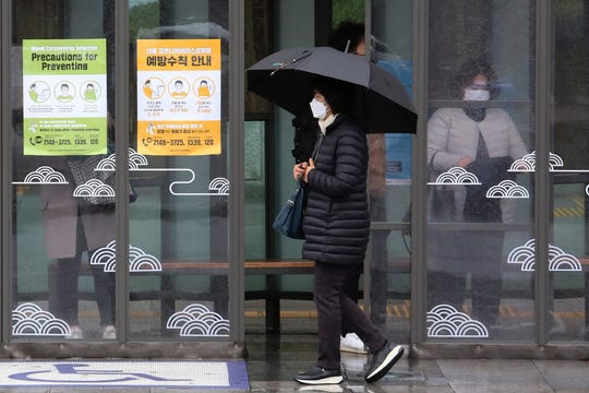 A woman wearing face mask passes by posters about precautions against new coronavirus at a bus station in Seoul, South Korea, Tuesday, Feb. 25, 2020.