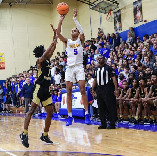 Wren junior Bryce McGowens(5) makes a three-pointer near Lower Richland guard Kyntrell Clinton during the first quarter of Class AAAA playoff game at Wren High School in Piedmont Tuesday. McGowens had 27 points in the first half and 32 for the game to help the Hurricanes win 74-69.