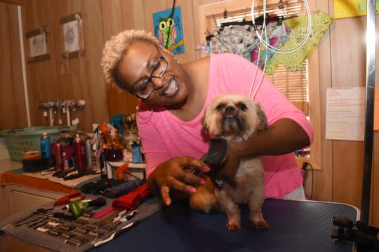 Chericia Thomas, owner of Kuttin It Up Dog Grooming Salon, grooms her dog T.J. Thomas started the business in 2012.