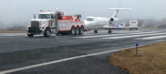 The plane that skidded off the runway at Monmouth Executive Airport in Wall gets towed to a hanger Wednesday morning, February 26, 2020, after it was pulled from a hillside at the end of the runway.  Five people who were aboard the plane were not injured in the incident that happened shortly before midnight.