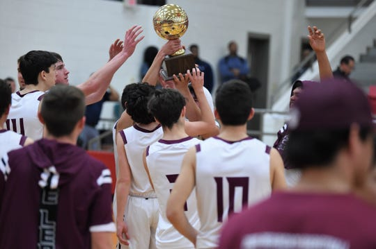The De Leon boys basketball team holds up the Region II-2A bi-district trophy after defeating Windthorst 65-60 in Mineral Wells on Tuesday. The Bearcats will face No. 6 Muenster in the area round.
