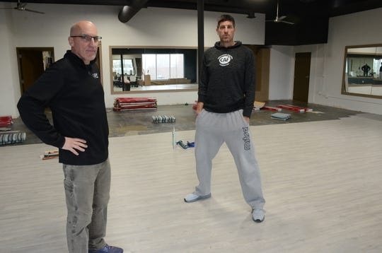 MIke Wood, left, and Sebastien Bellin in the top floor space still under construction above Wood's Battle Creek bicycle store where Bellin will operate Global Fit Industries.