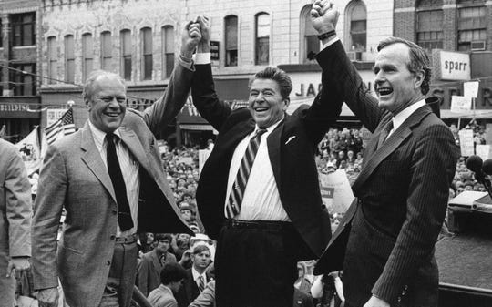 FILE - In this Nov. 3, 1980 file photo, former President Gerald Ford, from left, lends his support to Republican presidential candidate Ronald Reagan and his running mate George H.W. Bush in Peoria, Ill. The last Republican presidential candidate that California went for was George H.W. Bush. For both Oregon and Washington it was Ronald Reagan. Now, Republicans are struggling to hold seats in Congress, statehouses and city councils. (AP Photo, File)