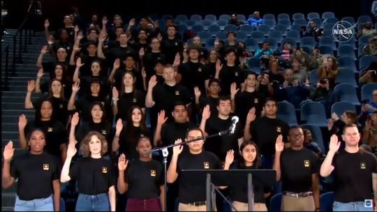 Recruits at Space Center Houston raise their right hand and repeat the oath of enlistment recited by NASA astronaut Andrew Morgan onboard the International Space Station.