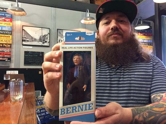 Queen City Brewery bar manager Jason Held holds a Bernie Sanders action figure at the Burlington business Feb. 25, 2020.