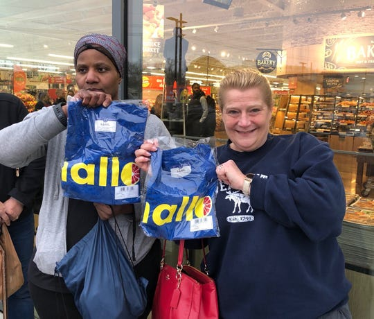Loretta Williams (left) of Haddon Heights and Francine Turner of Williamstown received Lidl T-shirts for being among the first shoppers in line for opening day Wednesday at the Cherry Hill store.