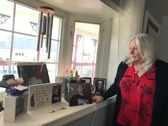 Roberta Arnold stands next to photos and mementos of her son, Kenny, who died of fentanyl toxicity in November 2018.