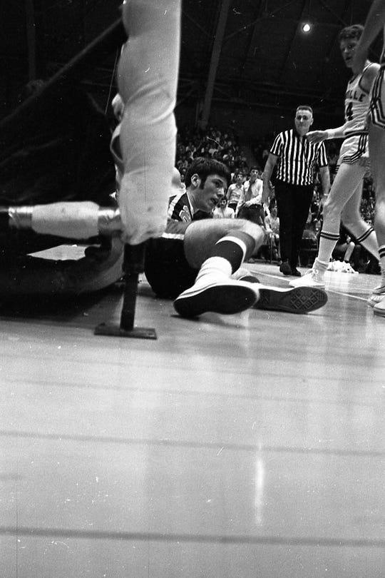 Zane Trace guard Tom Davis gets knocked out of bounds in the second quarter action. The Zane Trace Pioneers defeated the Granville Blue Aces in March 1970 in Class A tournament action at the Fairgrounds Coliseum in Columbus.