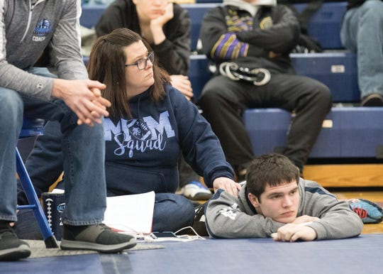 Dalton Metzger's mother, Jamie, rubs her son's shoulders as they wait for another Adena wrestler to compete during the SVC championships. Jamie had presented a proposal to the board to get wrestling recognized at Adena and still does much of the behind the scenes functions as well as keep stats for the team.