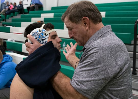 Keith Kauffman gives Dalton a slap on his head gear before he wrestles at a tournament at Huntington High School. It's a ritual both share that Kauffman rarely practices with other wrestlers.