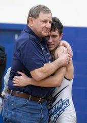 Adena wrestler Garrett Simmons hugs Coach Kauffman after an aggressive match against a Westfall wrestler at the SVC tournament at Southeastern High School.
