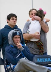 Keith Kauffman holds his granddaughter during a wrestling tri meet at Adena High School. Family is very important to the wrestling community who often spend several hours during the weekend with fellow wrestlers and their families.
