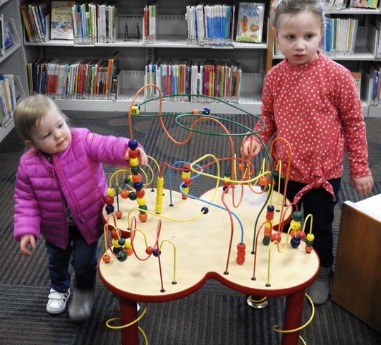 Ellie Conidi and Nora Vickers play with an educational toy in the children's room of the Coshocton Public Library.