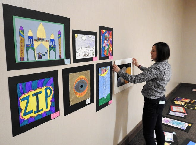 Jennifer Bush, executive director of the Johnson-Humrickhouse Museum, hangs art that is a part of the Playground of Color exhibit opening Sunday. The exhibit features pieces from elementary children across Coshocton County.