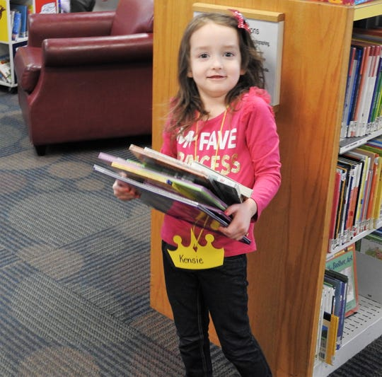Kensie Renner prepares to check out books in the children's room of the Coshocton Public Library. Visitors and use of physical materials were up for the library in 2019 over the previous year.