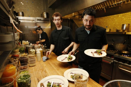 Chef Joe Tripp and line cook Ryan Skinner (back) deliver tasting menu items to customers Tuesday, Feb. 23, 2016, in the kitchen at Alba in Des Moines. Tripp was nominated for a James Beard Foundation award for his work at the East Village restaurant.