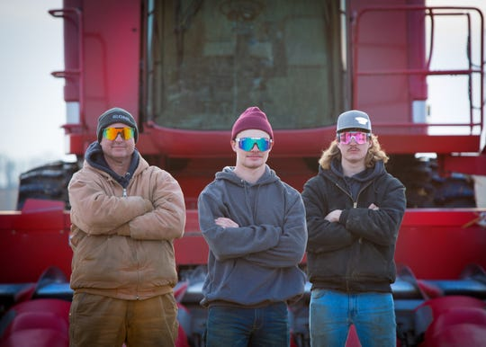 University of Northern Iowa grad Cole, middle, started a YouTube channel in 2018 chronicling his life on his family's farm. His father, Dale (left), often appears in the videos, along with Cole's brother Cooper (right).