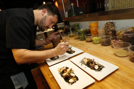 Chef Joe Tripp puts on the finishing touches Tuesday, Feb. 23, 2016, in the kitchen at Alba in Des Moines. Tripp was nominated for a James Beard Foundation award for his work at the East Village restaurant.
