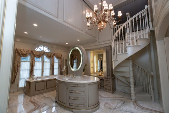The opulent owners' bath has a white onyx floor the owner found in Verona. The center Island supports an oval mirror that also is a television. The circular stairs at right lead up to a woman's large dressing room. Photographed in Bloomfield Hills, Tuesday, Feb. 25, 2020.