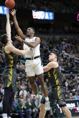 Michigan State Spartans forward Aaron Henry (11) scores against Iowa Hawkeyes forward Ryan Kriener (15) and  center Luka Garza (55) during first half action Tuesday, February 25, 2020 at the Breslin Center in East Lansing, Mich.
