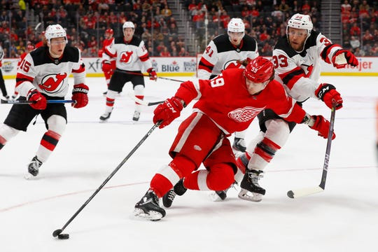 Detroit Red Wings left wing Tyler Bertuzzi (59) protects the puck from New Jersey Devils defenseman Fredrik Claesson (33) in the first period of an NHL hockey game Tuesday, Feb. 25, 2020, in Detroit. (AP Photo/Paul Sancya)
