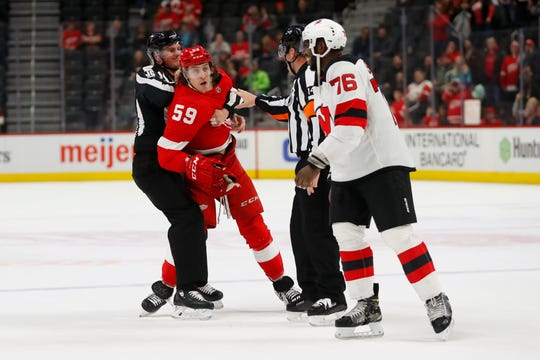 Detroit Red Wings left wing Tyler Bertuzzi (59) is held back by linesman Andy McElman (90) and referee Dennis LaRue (14) as New Jersey Devils defenseman P.K. Subban (76) skates off the ice in the third period of an NHL hockey game Tuesday, Feb. 25, 2020, in Detroit.