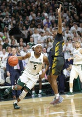 Michigan State Spartans guard Cassius Winston (5) drives against Iowa Hawkeyes guard Bakari Evelyn (4) during second-half action Tuesday, February 25, 2020 at Breslin Center in East Lansing, Mich.