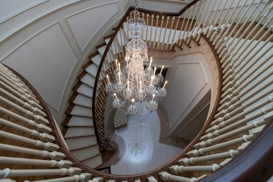 The graceful curving staircase is not a circle, but an ellipsis. Its elliptical lines continue and shape this part of the second floor. A crystal chandelier hangs in the center. The stairs are made from the builder's aged mahogany. Photographed in Bloomfield Hills, Tuesday, Feb. 25, 2020.