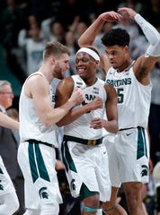 Michigan State's Kyle Ahrens, left, Cassius Winston, center, and Malik Hall celebrate during the second half. Michigan State won 78-70. (AP Photo/Al Goldis)