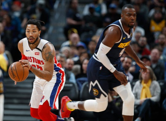 Detroit Pistons guard Derrick Rose, left, picks up a loose ball as Denver Nuggets forward Paul Millsap heads down the court to defend in the first half.
