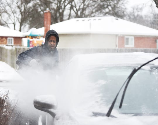 Freddie Williams Jr., 63, of Oak Park uses a leaf  blower to clean his neighbor's car on the 2300 block of Harding St. this morning.