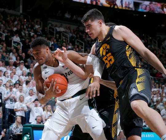 Michigan State's Xavier Tillman, left, and Iowa's Luka Garza fight for a rebound during the first half.
