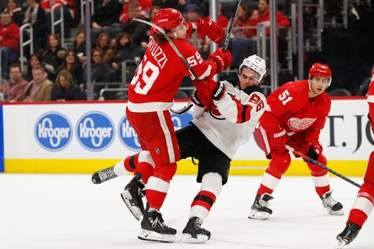 Detroit Red Wings left wing Tyler Bertuzzi checks New Jersey Devils center Jack Hughes off the puck in the second period Tuesday night.