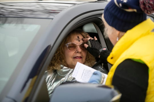 Parishioner Linda Taylor, right, dispenses ash on the forehead of Nancy Lambert, of Royal Oak, utilizing a drive-through lane during Ash Wednesday at St. David's Episcopal Church on Wednesday.