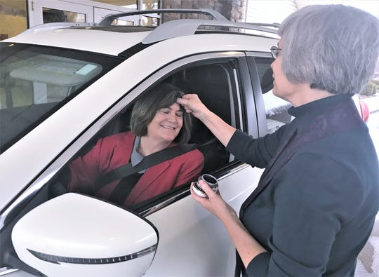 "Rev. Patricia Hubman, pastor at New Beginnings United Methodist Church in Elmira, applies ashes to the forehead of church member Suzie Rundell during the church's Ash Wednesday ""drive-through"" blessing."