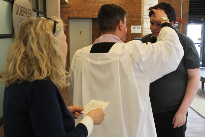 """Reagan Defriece of Vickery recieves ashes from the Rev. Matt Wahlgren during an """"Ashes to Go"""" service for Ash Wednesday held at Terra State Community College."""