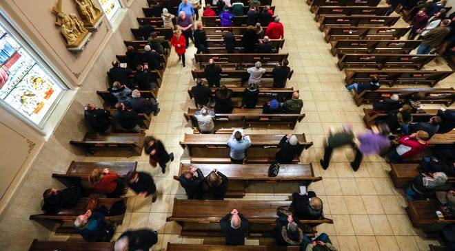 Scenes as congregation members take communion during the Ash Wednesday noon service on Wednesday, Feb. 26, 2020, at St. Willebrord Roman Catholic Church in Green Bay, Wis.