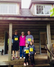 John Schopf Sr. (#36) and John Schopf Jr. (#35) pose with family members on the Schopf House porch, a historic log cabin located in Crossroads preserve and named after Schopf Sr.'s father.