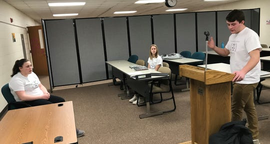 Playing an attorney for the plaintiff, Ben Naze questions witness Lindsey Livingston during a practice session for the Luxemburg-Casco High School mock trial team. Observing is Claire Delcore, another attorney for the plaintiff.
