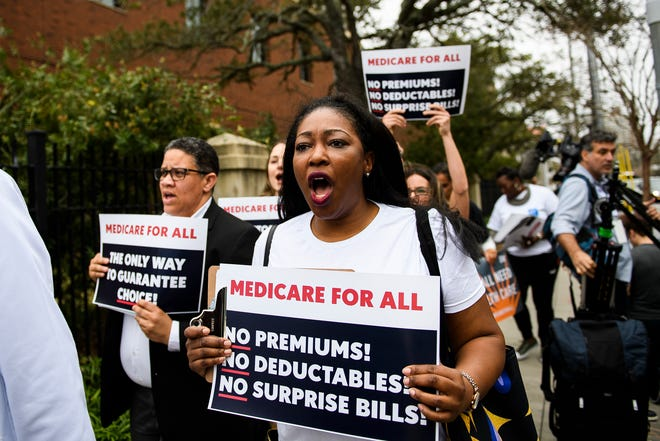 Protesters in support of Medicare for All march outside the South Carolina Democratic debate in Charleston on Feb. 25, 2020.